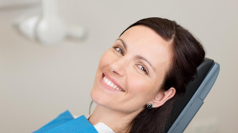 woman in dental chair | preventative dental cleanings and exams nederland tx