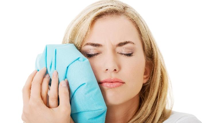 woman holding ice pack to her jaw | root canals nederland tx
